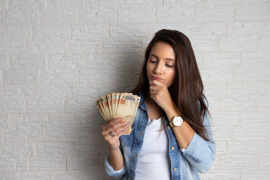 mulher pensando e olhando o dinheiro