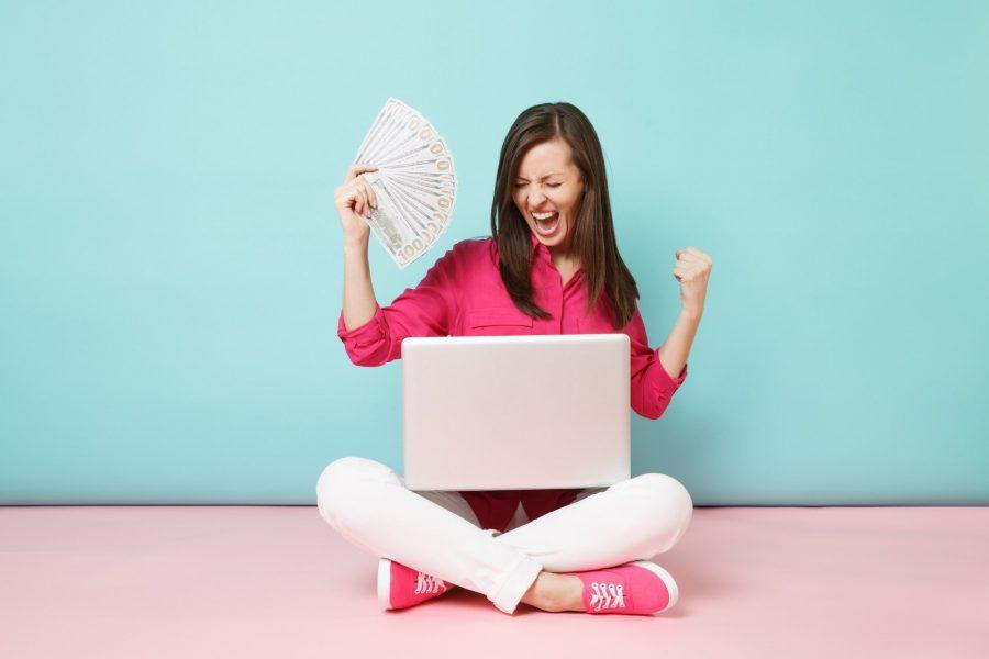 mulher feliz com dinheiro e no computador