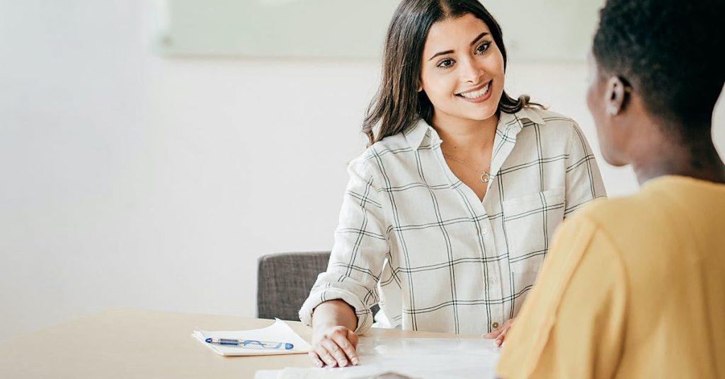 duas mulheres sentadas com papéis na mesa a sua frente