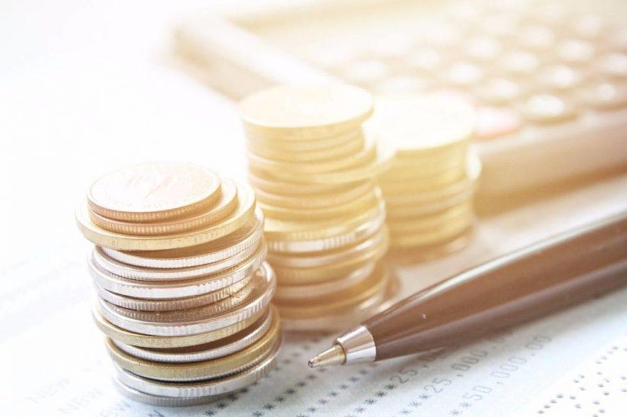moedas ao lado de uma caneta e uma calculadora
