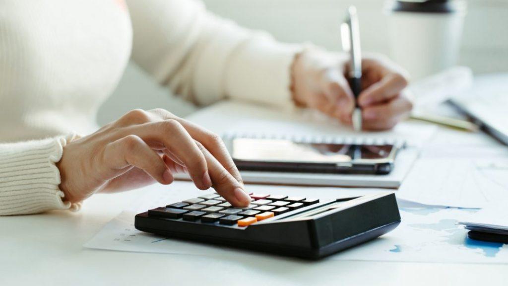 mulher utilizando uma calculadora